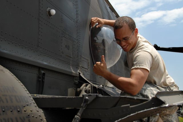 Spc. Joseph Greemore checks equipment on a CH-47 Chinook helicopter at Entebbe airfield prior to the start of Natural Fire 10.