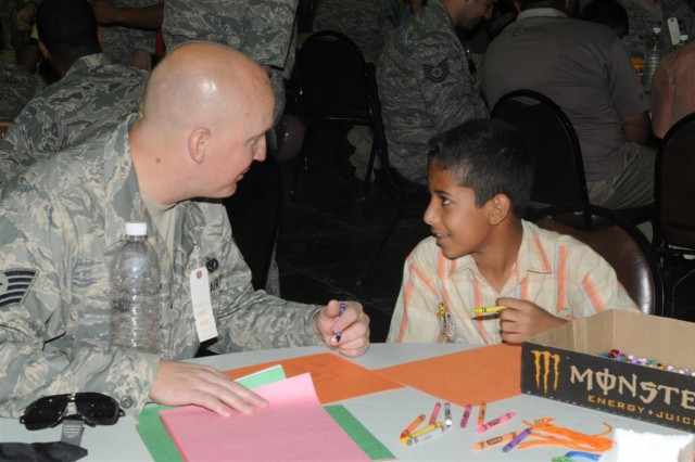 Air Force Tech. Sgt. Josh A. Sallee, the logistics civil augmentation program requirements manager for the 332nd Expeditionary Civil Engineer Squadron, and a Lake Geneva, Wis., native, colors with the child he is mentoring Oct. 10 at Iraqi Kids' Day, at the H-6 Morale, Welfare and Recreation center on Joint Base Balad, Iraq.