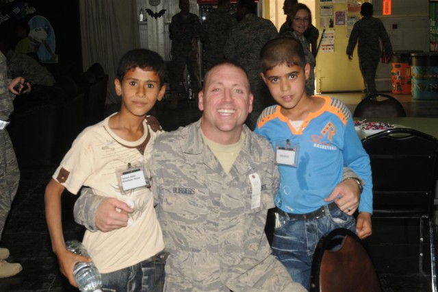 Air Force Tech. Sgt. Christopher J. Burgess, an electrical systems craftsman for the 332nd Expeditionary Civil Engineer Squadron and the director of operations for the Kids of Iraq program at Joint Base Balad, Iraq, poses with the two boys he mentored Oct. 10, at Iraqi Kids' day at the H-6 Morale, Welfare and Recreation center at JBB.