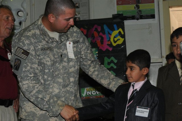 Spc. Matthew Harris, a supply specialist for the 23rd Ordnance Company and a Paducah, Ky., native, greets the child he is to mentor Oct. 10, at Iraqi Kids' Day at the H-6 Morale, Welfare and Recreation center at Joint Base Balad, Iraq.