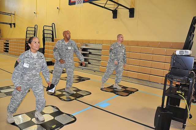 (From left) 1st Sgt. Rosalba Chambers, Sgt. 1st Class Timothy Harris, and Sgt. Seth Sutherland, try out the Dance Revolution, one of several activities available for teens at the center.