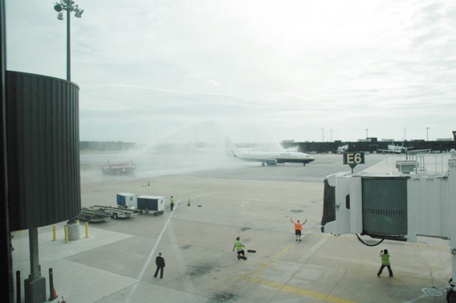 Fire engines from the BWI Airport fire department form a water cannon arch over a Miami Air charter flight carrying 90 Honor Flight Network World War II veterans as it taxis to its gate.