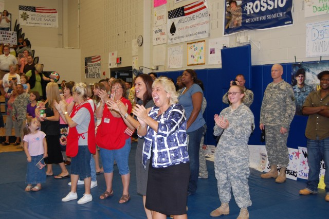 Battalion Commander Lt. Col. Mike Slocum 1st Battalion, 10th Aviation Regiment, 10th Mountain Division is greeted with a huge smile  from  his wife Kim (right center)  as he leads his troops into Tominac Fitness Center from a 12-month deployment to Iraq, Oct. 11.
