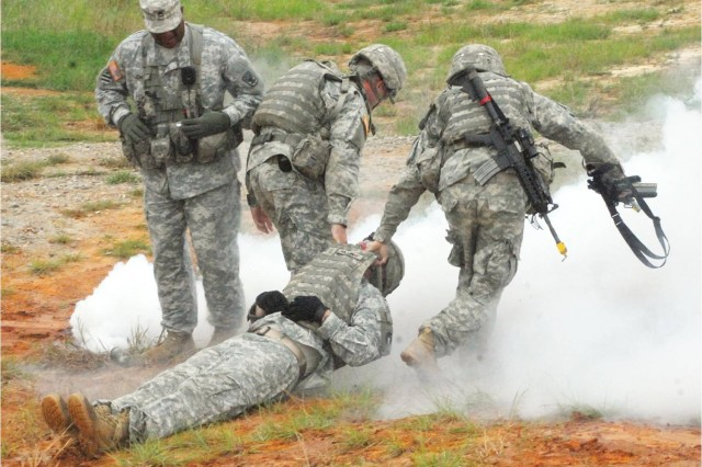 """SSG Ricardo Johnson watches as 2LT Anthony Vennekotler, acting as the medic, and 2LT Andrew Reyneso, acting as the platoon sergeant, pull 2LT Gerry Holloway toward a medical evacuation pick up point.  The lieutenants marked the evacuation point with smoke.  Holloway was """"wounded"""" when he failed to take cover during an explosion."""