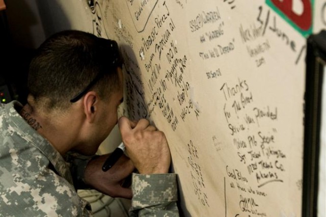 Retired Spc. Craig Chavez, who sustained multiple injuries as a result of an improvised explosive device detonation in 2006 including the loss of one eye and severe damage to the other, signs the wall at the Hero's Haven room of the Contingency Aero medical Staging Facility Oct. 14, at Joint Base Balad, Iraq.