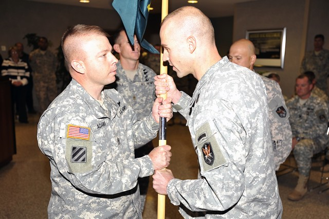 Maj. Jason Favero, new commander of the 1st Space Company (JTAGS), passes the company guidon back to 1st Sgt. Steven Adams during a change of command ceremony.