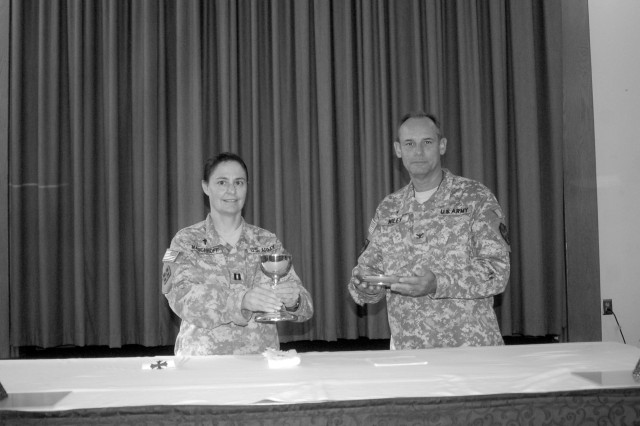 Capt. Karlyn Maschhoff, the 442nd Signal Battalion's chaplain (left) and Col. Craig Wiley Fort Gordon installation chaplain ready the sacraments.