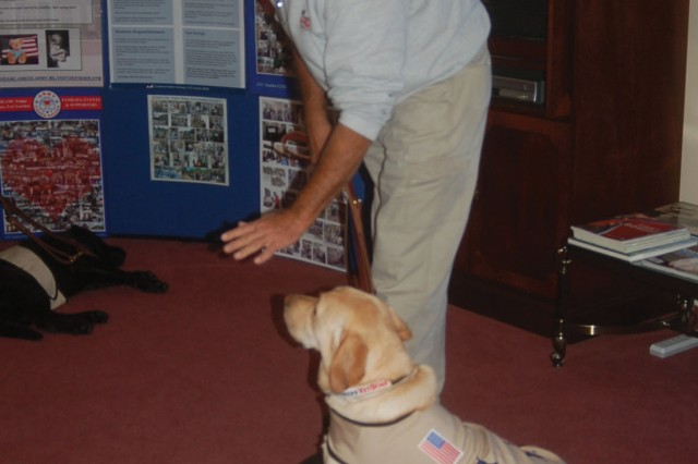 Mike Sergeant of America's VetDogs demonstrates handling techniques of Maverick, a therapy dog.
