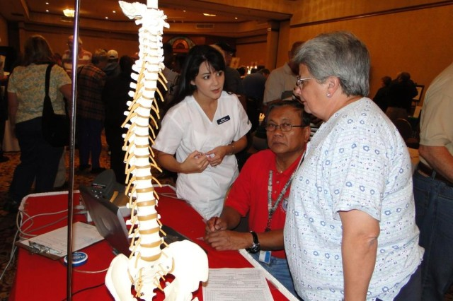 Health First chiropractic assistant Becky Fruendt talks to retired Master Sgt. Romero O'Campo and Rita Thaler about spine issues. Fruendt was able to take computer images of the spine so that she could review them with retirees at the Oct. 2 event. Both O'Campo and Thaler work for the AMCOM Cargo Directorate.