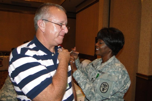 Fox Army Health Center's Sgt. 1st Class Delois Williams gives retired Chief Warrant Officer 4 Daniel Osborne a flu shot during the Military Retiree Appreciation Day event Oct. 2 at the Officers and Civilians Club. Fox gave more than 800 flu vaccines to retirees during the event. Osborne now works as a contractor for Aviation Reset at Redstone Arsenal.