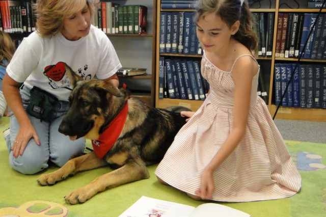 "Taka sits with 9-year-old Sofia Rundini and his owner and trainer, Jamie Ward, during Sofia's reading of ""Mary Had a Little Jam."" Sofia chose the book because one of the rhymes includes a dog."