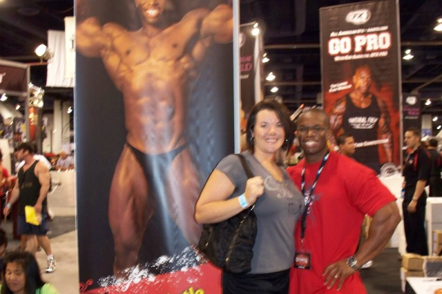 Sgt. 1st Class Heather Lytle, Regimental Support Squadron, 11th Armored Cavalry Regiment, and her husband Daron, pose next to a promotional poster featuring Daron. Daron Lytle is a professional bodybuilder and participates in competitions when not supporting the National Training Center as an electronics technician. (Photo courtesy of the Lytle Family)