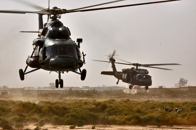 CAMP TAJI, Iraq-An MI-17 Hip helicopter (left) from the Iraqi Air Force and a UH-60 Black Hawk helicopter from 3rd Battalion, 227th Aviation Regiment, 1st Air Cavalry Brigade, 1st Cavalry Division, drop off Soldiers from the  34th Iraqi Army Brigade, 9th IA Division, during a joint air assault training mission, here, Oct. 17. The exercise showed the Iraqi ground troopers the assets their aviation counterparts bring to the fight and to familiarize the IA Soldiers in air insertion techniques.