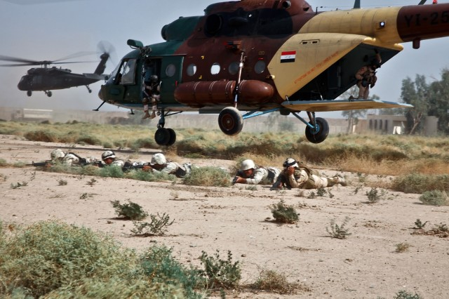CAMP TAJI, Iraq-Soldiers from the 34th Iraqi Army Brigade, 9th IA Division, stay low and take defensive positions after being air inserted into a simulated battlefield by an MI-17 Hip helicopter (right) from the Iraqi air force and a UH-60 Black Hawk helicopter from 3rd Battalion, 227th Aviation Regiment, 1st Air Cavalry Brigade, 1st Cavalry Division, Multi-National Division - Baghdad, during a joint training mission, here, Oct. 17. The two different aircraft flew together in formation before assaulting the landing zone.