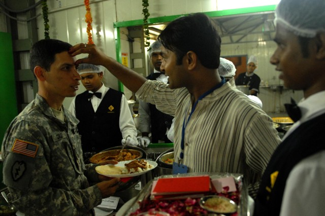 "CAMP BUNDELA, India (Oct. 16, 2009) - Rauol, head chef, places a ""third eye"" on Maj. Frankie Cruz, contracting officer assigned to the 411th Contracting Support Brigade, U.S. Forces, Korea, in honor of the Hindu celebration of Diwali, or the festival of lights at Camp Bundela, Oct. 17. The Soldiers assigned to 2nd Squadron, 14th Cavalry Regiment, ""Strykehorse,"" 2nd Stryker Brigade Combat Team, 25th Infantry Division, from Schofield Barracks, Hawaii were also treated to a Southern Indian feast in honor of the Hindu festival. The Soldiers are currently at Camp Bundela, India participating in exercise Yudh Abhyas 09. YA09 is a bilateral exercise involving the Armies of India and the United States. The primary goal of the exercise is to develop and expand upon the relationship between the Indian and U.S. Army."