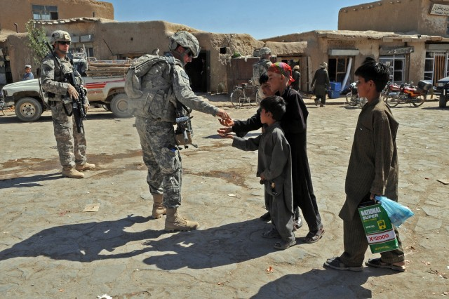 Paratroopers with 3rd Platoon, Company A, 1st Battalion, 501st Infantry Regiment, hand candy to local children while on patrol in the Waza Kwah bazaar Oct. 2 in the Paktika Province of eastern Afghanistan.