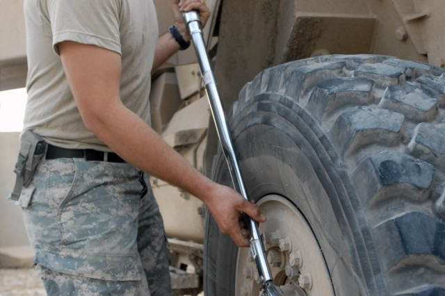 BAGHDAD - Pasco, Wash. native, Sgt. Luke Mehling, a tank mechanic assigned to Company B, 2nd Battalion, 5th Cavalry Regiment, 1st Brigade Combat Team, 1st Cavalry Division, tightens a bolt after replacing a tire on a Mine-Resistant Ambush-Protected vehicle at Joint Security Station War Eagle, Oct. 16.