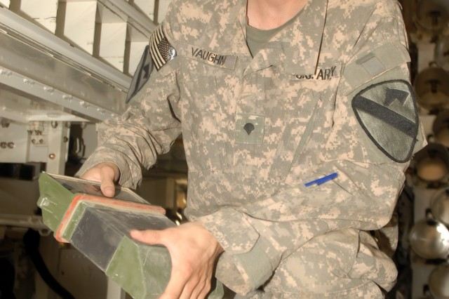 BAGHDAD - Spc. Robert Vaughn, of Omaha, Neb., inspects dismounted periscopes inside an ammunition carrier at Camp Taji, here, Oct. 19.