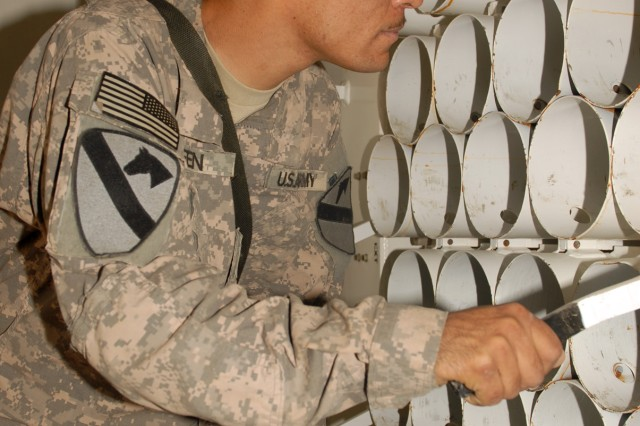 BAGHDAD - Sgt. Matthew Keen, of San Antonio, Texas, checks tubes used for holding shells in an ammunition carrier at Camp Taji, here, Oct. 19.