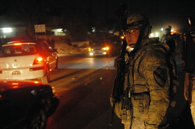 BAGHDAD - Sgt. Aron Stanley, a tanker from Snyder, Texas, assigned to Company C, 2nd Battalion, 5th Cavalry Regiment, 1st Brigade Combat Team, 1st Cavalry Division, waits for traffic before crossing during a joint patrol to prevent insurgents from launching indirect fire at forward operating bases in Baghdad, Oct. 18.
