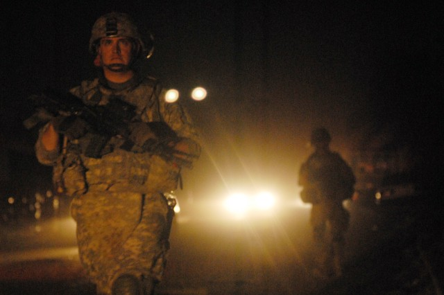 BAGHDAD - Sgt. Ryan Tullis, a forward observer from Gillette, Wyo., assigned to Company C, 2nd Battalion, 5th Cavalry Regiment, 1st Brigade Combat Team, 1st Cavalry Division, patrols the night with Iraqi Army Soldiers during a joint patrol in eastern Baghdad, Oct. 18.