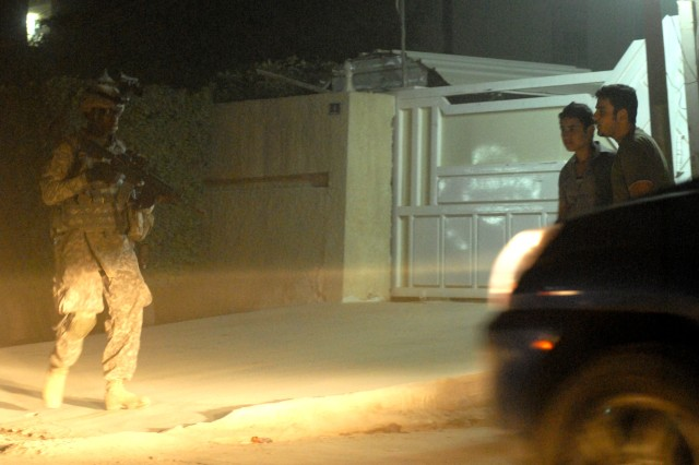 BAGHDAD - On his third tour to Baghdad, Sgt. Steven Barner, a tank gunner from Greenwood, Miss., assigned to Company C, 2nd Battalion, 5th Cavalry Regiment, 1st Brigade Combat Team, 1st Cavalry Division, patrols the night while two Iraqi teenagers hang out during a joint patrol in eastern Baghdad, Oct. 18.