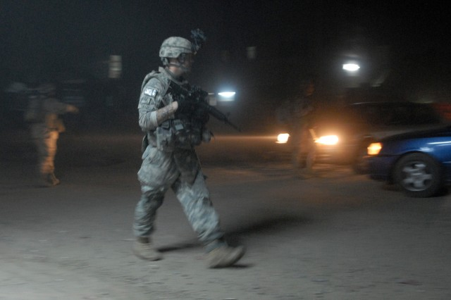 BAGHDAD - As cars pass by in eastern Baghdad, Oct. 18, Sgt. Ryan Tullis (center), a forward observer from Gillette, Wyo., assigned to Company C, 2nd Battalion, 5th Cavalry Regiment, 1st Brigade Combat Team, 1st Cavalry Division, patrols with IA Soldiers during an operation to deter insurgents from shooting indirect fire.