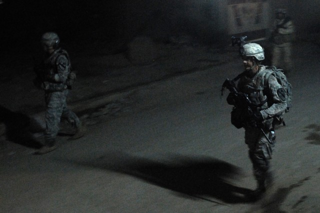 BAGHDAD - Sgt. Robert Willard (right), a tanker from Pulaski, Va., assigned to Company C, 2nd Battalion, 5th Cavalry Regiment, 1st Brigade Combat Team, 1st Cavalry Division, walks the dark streets of eastern Baghdad with his IA counterparts during a joint patrol to secure the area outside of Joint Security Station Shield, here, Oct. 18.