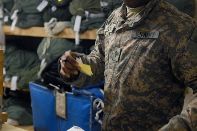 BAGHDAD - Long Beach, Calif. Native, Spc. Clifton Simon, laundry maintenance specialist assigned to the 488th Quartermaster Company, attached to the 1st Brigade Combat Team, 1st Cavalry Division, inspects a Soldier's laundry ticket in order to locate the laundry bag at Joint Security Station War Eagle, Oct. 18.