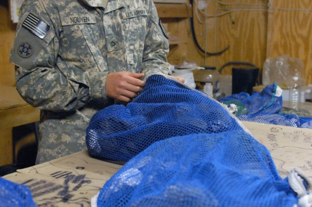 BAGHDAD- San Diego native, Spc. Scott Allen, a laundry maintenance specialist assigned to the 488th Quartermaster Company, attached to the 1st Brigade Combat Team, 1st Cavalry Division, loads laundry into bags for washing at Joint Security Station War Eagle Oct. 18.