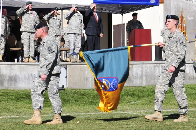 Col. Greg  Bowen, Commander, 100th Missile Defense Brigade (Ground-based Midcourse), and Staff Sgt. Andrew Knight, Intelligence Analyst/ Unit Color Bearer, 100th MDB, lead the 100th's formation past (from left to right on stage) Brig. Gen. Thomas Mills, Outgoing Commander, Colorado Army National Guard, Col. (P)  Dana Capozzella, Incoming COARNG, Air Force Maj. Gen. H. Michael Edwards, The Adjutant General of Colorado and Colorado Governor Bill Ritter during a pass and review at a change of command ceremony at  Infiniti Park Stadium in Glendale, Colo.