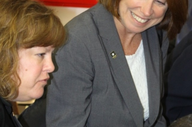 Jo-Ellen Darcy, Assistant Secretary of the Army for Civil Works, and Cathy Van Arsdale with the Corps of Engineers St. Louis District, watch employees at the Veterans Curation Project lab in Augusta, Ga.
