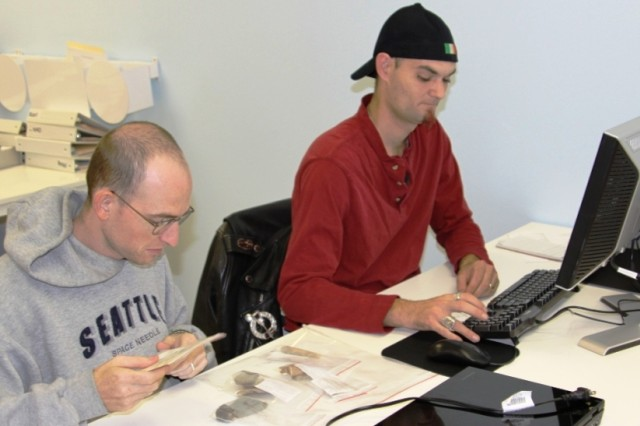 Benjamin Berkman, left, examines artifacts while Christopher Bowman enters information about the artifacts into a database. Both men are veterans employed at the Veterans Curation Project in Augusta, Ga.
