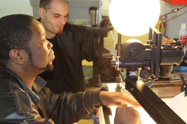 Reginold Fryson positions an artifact under a digital copy camera as Christopher Bowman steadies the platform. Both men are veterans employed at the Veterans Curation Project in Augusta, Ga.
