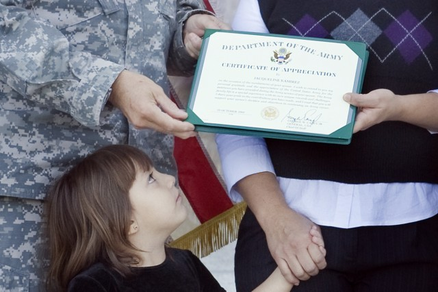 The daughter of Jacqueline Ramirez looks at the Certificate of Appreciation her mother was awarded by Gen. George W. Casey Jr., as part of her father's reenlistment ceremony in Ft. Benning, Ga., Oct. 20, 2009.