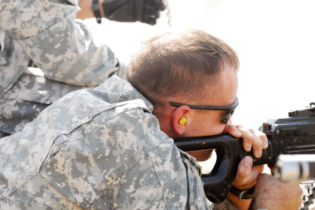 Sgt. Robert Brown fires a machine gun at a range on the Iraqi Special Operations Forces compound at Baghdad's Victory Base Complex Oct. 16. In 2006, Brown, a Moncks Center, S.C., native, lost his right leg below the knee in an attack. He returned to Iraq Oct. 11, as part of the Operation Proper Exit program, which allows wounded servicemembers to return to the places they were injured and to see the changes that have been made since they were last in theater.