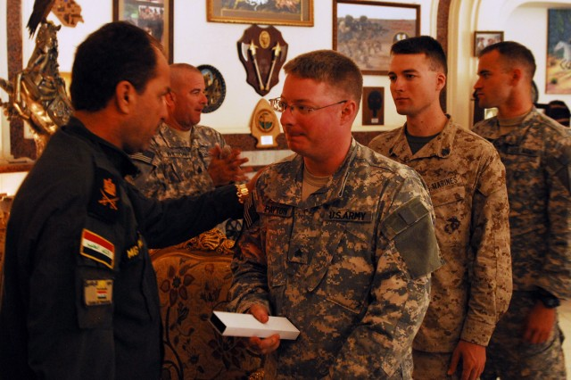Maj. Gen. Fadhil Barwari (left), commander of 1st Brigade, Iraqi Special Operations Forces, presents Sgt. Ethan Payton, a Milford, N.J. native, with a token of appreciation Oct. 16, at the Iraqi Special Operations Forces' compound in Baghdad. Payton's left arm was amputated below the elbow after he was hit by a rocket propelled grenade during an ambush June 2004 in Baghdad.