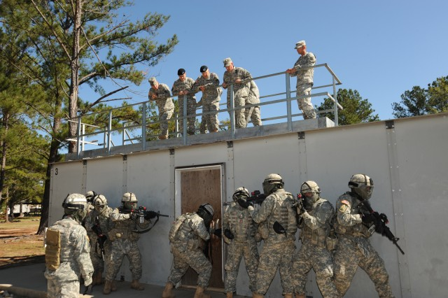 Army Chief of Staff Gen. George W. Casey Jr., center right, and Maj. Gen. Michael Ferriter, center left, Fort Benning's commanding general, watch a squad of Soldiers with C Company, 1st Battalion, 19th Infantry Regiment, 198th Infantry Brigade, practice entering a building during urban operations training on Oct. 20.