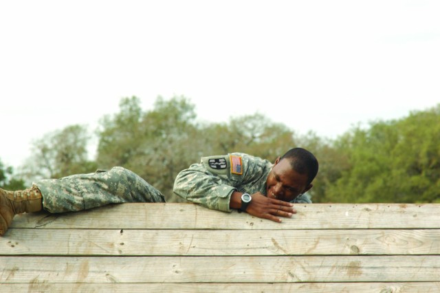 Staff Sgt. Benjamin D. Buford clambers over a reversed wall during the obstacle course portion of the Expert Field Medical Competition at Camp Bullis, Texas. Buford is an instructor/writer for the Army Medical Department Center and School at Fort Sam Houston, Texas.