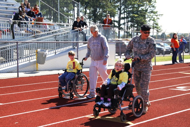 Sgt. Sophia Malone helps her athlete, Hanah Zvaiter, 11, of Rainbow Elementary School, in the assisted 50-meter wheelchair race at Special Olympics Oct. 20 in Huntsville, Ala.