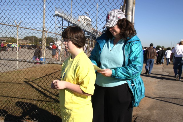 Susan McRae, a USASMDC/ARSTRAT employee, looks at her niece's competition information to see what events she will be competing in at Special Olympics Oct. 20 in Huntsville, Ala.