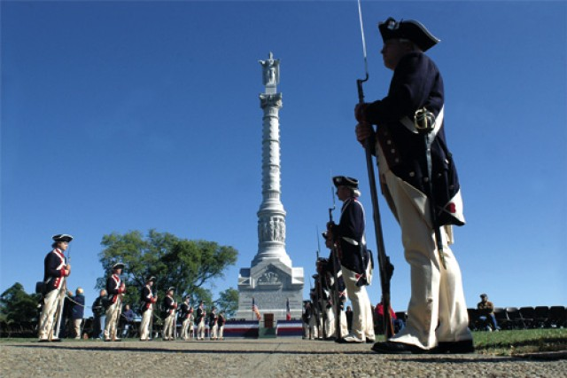 Soldiers from the Commander-in-Chief's Guard, 3rd Army Inf. Rgt.,  line up along the walkway in front of the Yorktown Victory Monument. The monument symbolizes the victory over the British forces through the American-French alliance during the American Revolution.