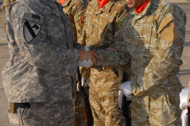 BAGHDAD - Staff Sgt. Nicky Green, the noncommissioned officer in charge of the training for the Karkh Area Command Advisory Team, assigned to D Troop, Division Special Troops Battalion, 1st Cavalry Division, shakes hands with graduates of the six-week long training course for the KAC Strike Team, Oct. 19..