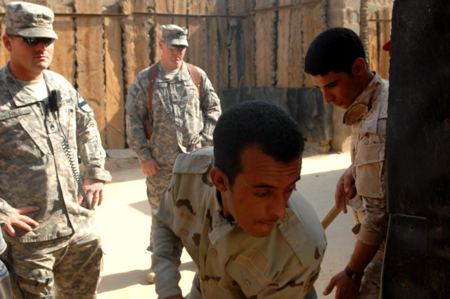 BAGHDAD - Staff Sgt. Dustin Rice (left), from St. Paul, Neb., and Staff Sgt. Kirk High (background right), from Fort Worth, Texas, both course instructors, watch Iraqi Army Soldiers enter a doorway during a mock-room clearing exercise at Joint Security Station Shield, here, Oct. 19.