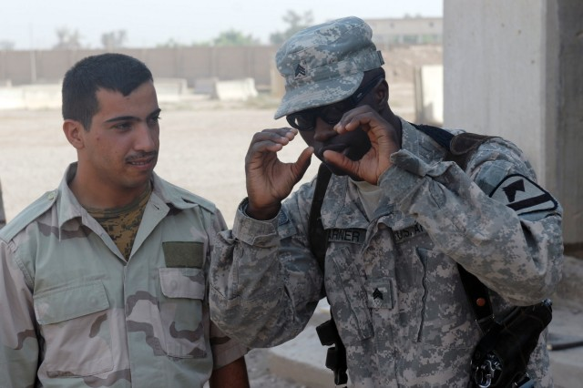 BAGHDAD - On his third tour to Baghdad, Sgt. Steven Barner (right), a tank gunner from Greenwood, Miss., explains what to look for while on patrol to an Iraqi Army Soldier during a training academy at Joint Security Station Shield, here, Oct. 18.