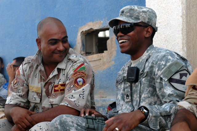 BAGHDAD - Staff Sgt. Avery Washington (right), a section sergeant from Atlanta, Texas, shares a laugh with an Iraqi Army counterpart during a break from a training academy at Joint Security Station Shield, Oct. 18.