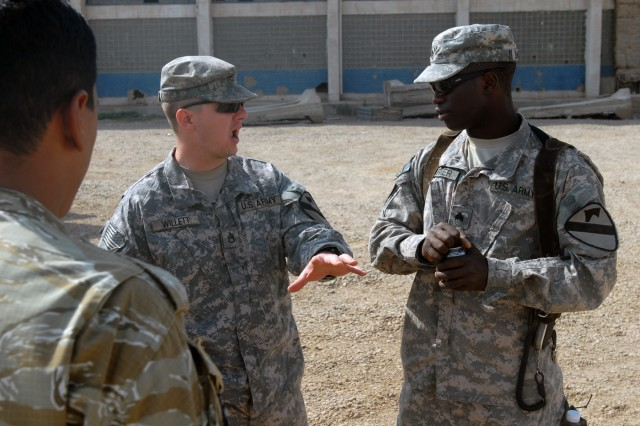 BAGHDAD - Staff Sgt. Joseph Willett (left), a section sergeant from Evansville, Ind., talks with Sgt. Steven Barner, a tank gunner from Greenwood, Miss., during an Iraqi Army training Academy. The Soldiers have been together most of their Army career and are on their third tour to Baghdad together.