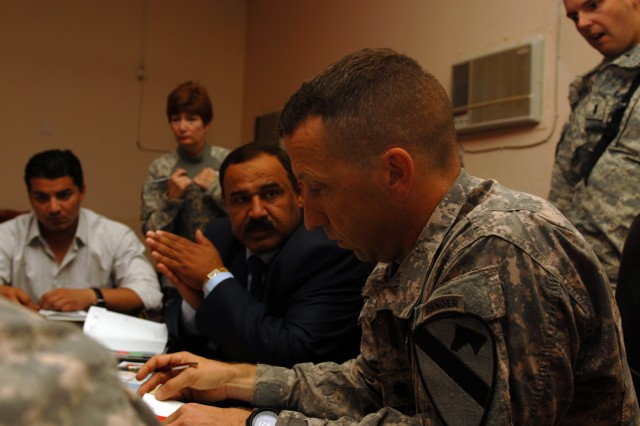 CAMP TAJI, Iraq - Khassim Khalifa, (left) and Lt. Col. Scott Jackson, of Fort Hood, Texas, discuss a list of projects proposed by the Tarmiyah Council during a key leader engagement, here, Oct. 20. Jackson, who commands 1st Battalion, 5th Cavalry Regiment, 1st Brigade Combat Team, 1st Cavalry Division, helps provide guidance about how much aid could be provided for projects such as a bank, healthcare center and fire department.