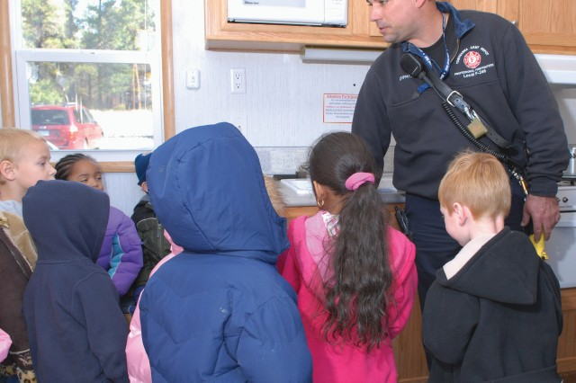 Keith DiPatri, firefighter, teaches children from the Child Development Center about fire safety and how to escape from a burning building. He works in the Industrial Risk Management Directorate's Fire and Emergency Services Division.