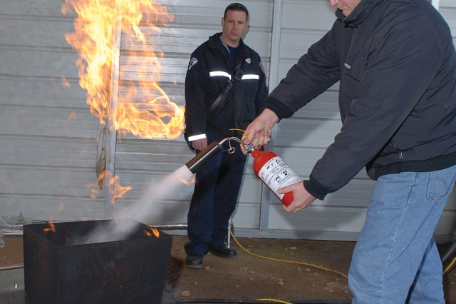 Firefighter Palmer Johnson instructs Brian Brogan, electronics mechanic, in the Communication Systems Directorate's Tactical Satellite Systems Branch, on the proper use of a fire extinguisher. He works in the Industrial Risk Management Directorate's Fire and Emergency Services Division.